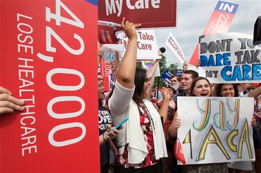 """Jessica Ellis, right, with """"yay 4 ACA"""" sign, and other supporters of the Affordable Care Act, react with cheers as the opinion for health care is reported Washington June 25, 2015. (AP Photo/Jacquelyn Martin)"""