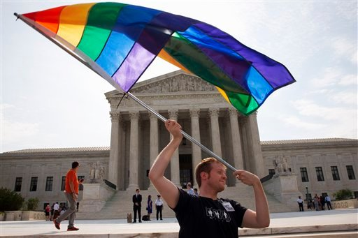 John Becker, 30, of Silver Spring, Md., waves a rainbow flag in support of gay marriage outside of the Supreme Court in Washington, Thursday June 25, 2015. (AP Photo/Jacquelyn Martin)