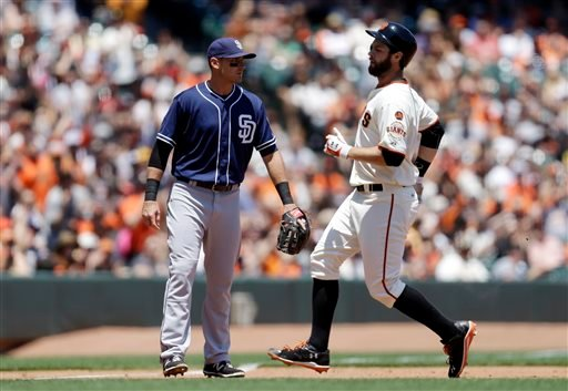San Francisco Giants' Brandon Belt, right, tags up at third base beside San Diego Padres' Will Middlebrooks with a stand up triple in the fourth inning of a baseball game, Thursday, June 25, 2015, in San Francisco.