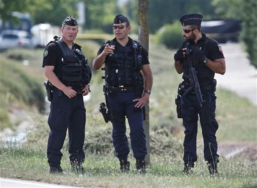 Police officers guard the road leading to a plant where an attack took place in Saint-Quentin-Fallavier, southeast of Lyon, France, Friday, June 26, 2015. (AP Photo/Michel Euler)