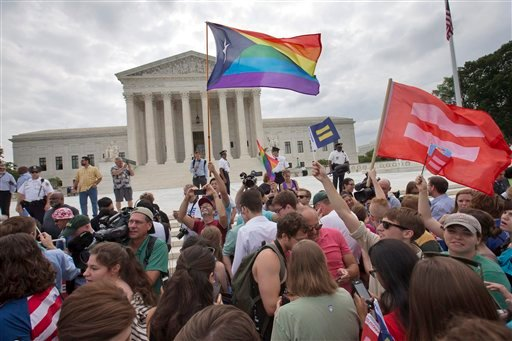 The crowd reacts as the ruling on same-sex marriage was announced outside of the Supreme Court in Washington, Friday June 26, 2015. The Supreme Court declared Friday that same-sex couples have a right to marry anywhere in the US. (AP Photo/Jacquelyn Marti