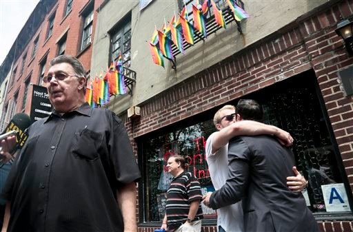Stonewall Inn's bartender who goes by the single name of Tree, far left, is interviewed while a couple, requesting anonymity, kiss outside the iconic Greenwich Village bar June 26, 2015, in New York (AP Photo/Bebeto Matthews)
