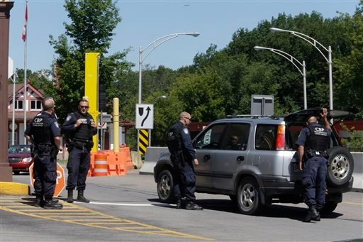 Canadian Boarder Patrol Officers search a car crossing into Canada for convicted murderers Richard Matt and David Sweat, Friday, June 26, 2015 in Constable, N.Y. Authorities shifted a focus of their three week search closer to the Canadian border. (AP Pho
