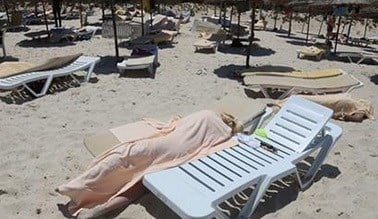 Bodies are covered on a Tunisian beach, in Sousse, Friday June 26, 2015. A young man unfurled an umbrella and pulled out a Kalashnikov, opening fire on European sunbathers in an attack that killed at least 28 people at a Tunisian beach resort - AP