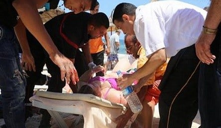 © Injured people are treated on a Tunisian beach, in Sousse, Friday June 26, 2015. A young man unfurled an umbrella and pulled out a Kalashnikov, opening fire on European sunbathers in an attack that killed at least 28 people at a Tunisian beach resort —