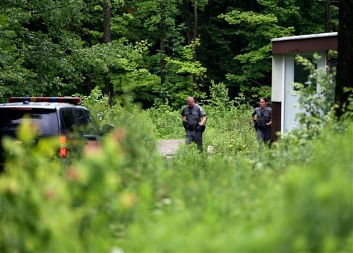 New York State Police troopers search a camp on Sunday, June 28, 2015, in Malone, N.Y. The shooting death of one escaped killer brought new energy to the three-week hunt for a second escaped murderer in the United States as helicopters, search dogs and hu
