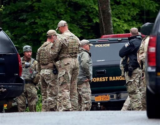 Law enforcement officers gather on a road on Sunday, June 28, 2015, in Malone, N.Y. The shooting death of one escaped killer brought new energy to the three-week hunt for a second escaped murderer in the United States as helicopters, search dogs and hundr