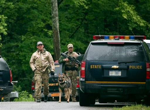 Law enforcement officers walk along a road on Sunday, June 28, 2015, in Malone, N.Y. The shooting death of one escaped killer brought new energy to the three-week hunt for a second escaped murderer in the United States as helicopters, search dogs and hund