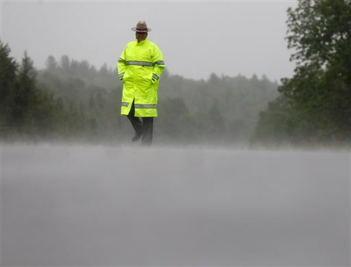 A New York State Police trooper stands in the rain at a roadblock on Sunday, June 28, 2015, in Malone, N.Y. The shooting death of one escaped killer brought new energy to the three-week hunt for a second escaped murderer in the United States as helicopter