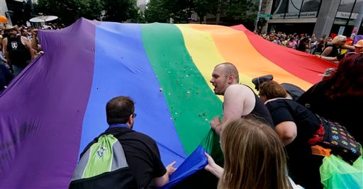 Volunteers reach to collect money that was tossed into a giant rainbow flag donated for parade expenses at the 41st annual Pride Parade Sunday, June 28, 2015, in Seattle. Large turnouts were expected for gay pride parades across the U.S. following the lan