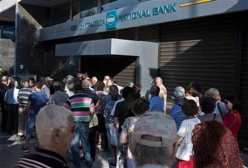Elderly people, who usually get their pensions at the end of the month, wait outside a closed bank in Athens June 29, 2015. (AP Photo/Petros Giannakouris)