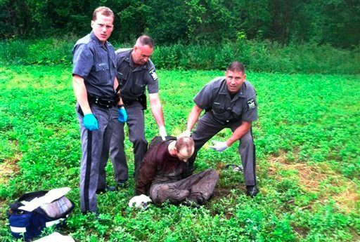Police stand over David Sweat after he was shot and captured near the Canadian border Sunday, June 28, 2015, in Constable, N.Y. (AP Photo)