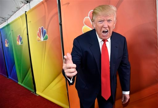 """In this Jan. 16, 2015 file photo, Donald Trump, host of the television series """"The Celebrity Apprentice,"""" mugs for photographers at the NBC 2015 Winter TCA Press Tour in Pasadena, Calif."""