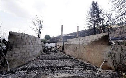 © The foundation and chimneys from a destroyed home remain following a wildfire the night before, Monday, June 29, 2015, in Wenatchee, Wash.