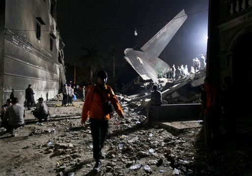 Rescuers search for victims at the site where an Indonesian air force cargo plane crashed in Medan, North Sumatra, Indonesia, Tuesday, June 30, 2015.