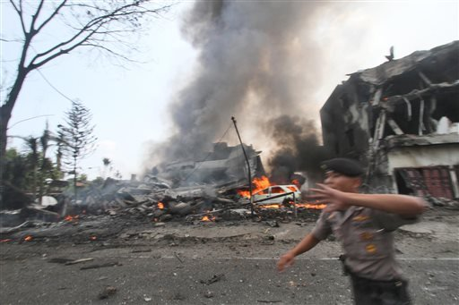 A police officer gestures at the crowd near the site where an Air Force cargo plane crashed in Medan, North Sumatra, Indonesia, Tuesday, June 30, 2015.