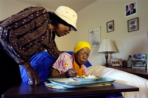 In this Monday, June 22, 2015 photo, Lois Judge, left, helps her aunt Susannah Mushatt Jones, 115, during breakfast in Jones' room at the Vandalia Avenue Houses, in the Brooklyn borough of New York.