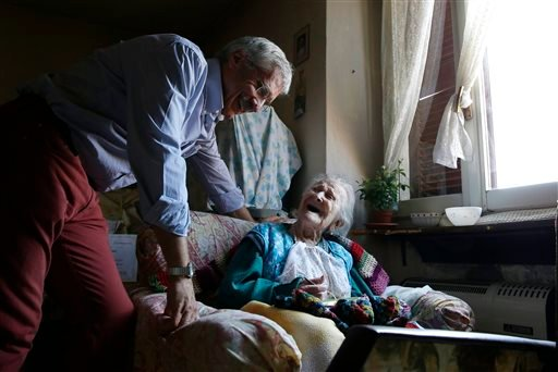 In this Friday, June 26, 2015 photo, Emma Morano, 115, smiles at her physician, Carlo Bava, in her apartment in Verbania, Italy.