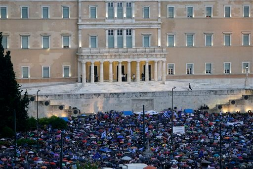 Demonstrators gather under the rain during a rally organized by supporters of the YES vote to the upcoming referendum, at Syntagma Square in Athens, Tuesday, June 30, 2015.