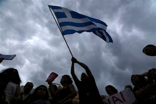 A demonstrator waves a Greek flag during a rally organized by supporters of the YES vote to the upcoming referendum in Athens, Tuesday, June 30, 2015.