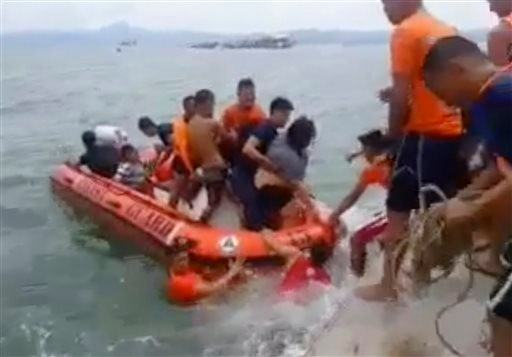 In this image made from video, rescuers help passengers from a capsized ferry boat, rear, in Ormoc city on Leyte Island, Philippines, Thursday, July 2, 2015.