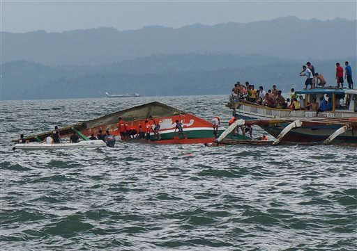 Rescuers help passengers from a capsized ferry boat, center, in Ormoc city on Leyte Island, Philippines, Thursday, July 2, 2015.