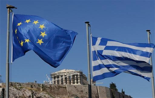 The Greek, right, and the European flags wave under the ancient Acropolis hill in Athens, Sunday, July 5, 2015. Greeks lined up at polling stations and ATMs alike Sunday as the country voted on its financial future, choosing in a referendum whether to acc