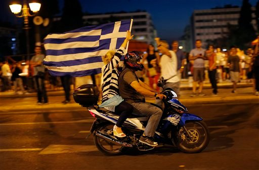 A supporter of the No vote waves a Greek flag after the first results of the referendum at Syntagma square in Athens, Sunday, July 5, 2015. Greece faced an uncharted future as its interior ministry predicted Sunday that more than 60 percent of voters in a