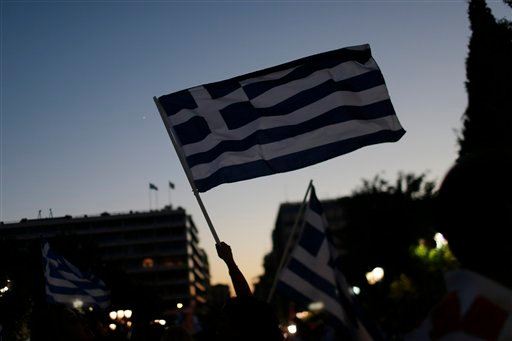 Supporters of the No vote wave Greek flags after the first results of the referendum at Syntagma square in Athens, Sunday, July 5, 2015. Greece faced an uncharted future as officials counted the results of a referendum Sunday on whether to accept creditor