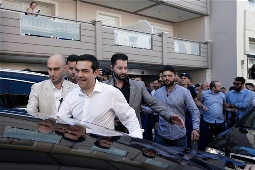 Greece's Prime Minister Alexis Tsipras, foreground, is escorted by police officers after voting at a polling station in Athens, Sunday, July 5, 2015. Greeks were voting Sunday in a bailout referendum that will decide the country's future, with opinion pol