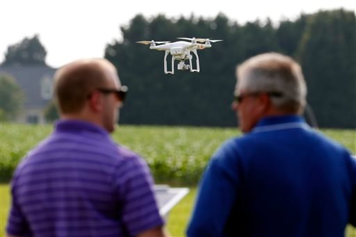 In this June 11, 2015 photo, a DJI Phantom 3 drone is flown by Matthew Creger, left, marketing director for Intelligent UAS, as he talks with Chip Bowling, from Newburg, Md., president of the National Corn Growers, during a drone demonstration at a farm a