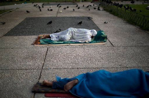 "Homeless sleep on the ground in central Athens, Monday, July 6, 2015. Greece's finance minister has resigned following Sunday's referendum in which the majority of voters said ""no"" to more austerity measures in exchange for another financial bailout. (AP"
