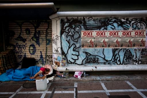 "A homeless sleeps at the entrance of a closed store with posters reading ''No'' in central Athens, Monday, July 6, 2015. Greece's Finance Minister Yanis Varoufakis has resigned following Sunday's referendum in which the majority of voters said ""no"" to mor"
