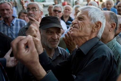 Elderly people argue with a bank worker as they wait to be allowed into the bank to withdraw a maximum of 120 euros ($134) for the week in Athens, Monday, July 6, 2015. Greece's Finance Minister Yanis Varoufakis has resigned following Sunday's referendum