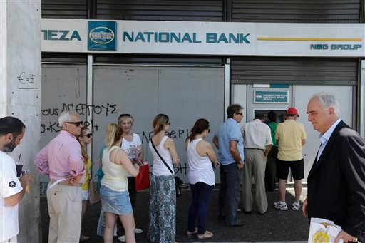 People line up to use ATM machines of a bank after government's decision for limited daily cash withdrawals to 60 euros ($67), in Athens, on Monday, July 6, 2015. Greek Finance Minister Yanis Varoufakis resigned Monday, saying he was told shortly after Gr