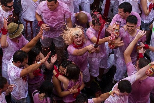 """Revelers throw wine during the launch of the """"Chupinazo"""" rocket, to celebrate the official opening of the 2015 San Fermin festival in Pamplona, Spain, Monday, July 6, 2015. Revelers from around the world turned out here to kick off the festival with a mes"""