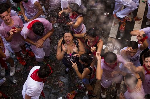 """Revelers celebrates as people throw water from the balconies during the launch of the """"Chupinazo"""" rocket, to celebrate the official opening of the 2015 San Fermin festival in Pamplona, Spain, Monday, July 6, 2015. Revelers from around the world turned out"""