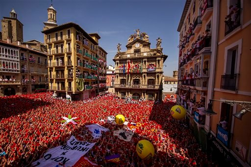 """Revelers hold up traditional red neckties during the launch of the """"Chupinazo"""" rocket, to celebrate the official opening of the 2015 San Fermin fiestas in Pamplona, Spain, Monday, July 6, 2015. Revelers from around the world turned out here to kick off th"""
