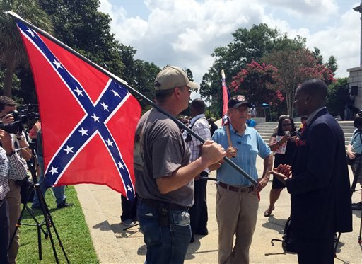 Randy Saxon, left and Wayne Whitfield, both of Anderson, S.C., discuss the Confederate flag on the South Carolina Statehouse grounds with Brodrick S. Hall of Atlanta, right, on Monday, July 6, 2015.