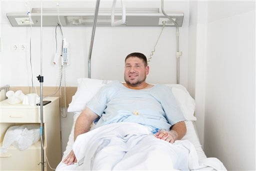 Mike Webster, a 38-year-old occupational therapist from Gainesville, Florida, who was gored in the armpit while running with the bulls in Pamplona for the 38th time over the last 11 years, poses for a picture on his hospital bed in Pamplona, Spain.