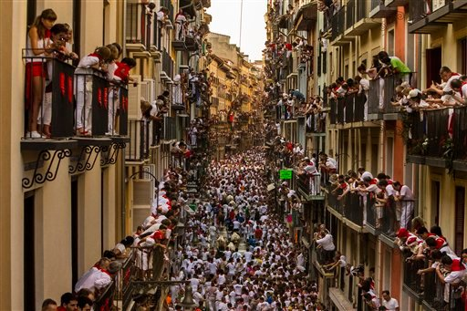 People watch as Jandilla fighting bulls and revelers run during the running of the bulls at the San Fermin festival in Pamplona, Spain, Tuesday, July 7, 2015.