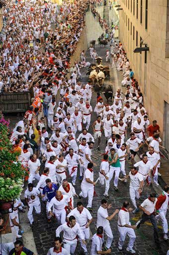People watch participants run ahead of ''Jandilla'' fighting bulls from Santo Domingo street during the running of the bulls at the San Fermin Festival, in Pamplona, Spain, Tuesday, July 7, 2015.