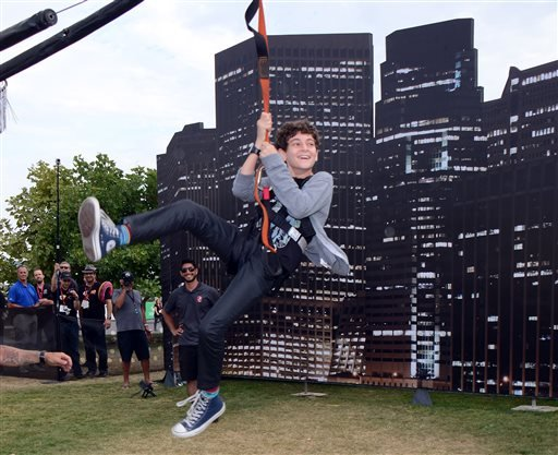 """In this July 26, 2014 file photo, David Mazouz ziplines at the """"Gotham"""" press line on Day 3 of Comic-Con International in San Diego, Calif."""