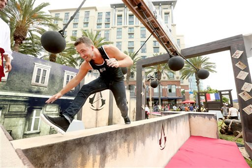 In this July 25, 2014 file photo provided by Ubisoft, Stephen Lunsford runs the parkour course at Ubisoft's Assassin's Creed Experience during Comic-Con, in San Diego.