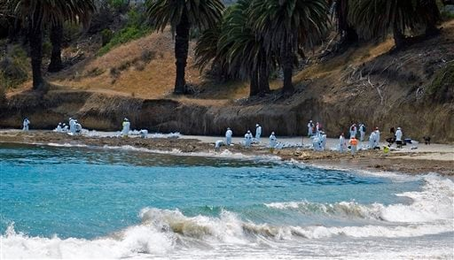 In this May 22, 2015 file photo cleanup crews rake and shovel oil-contaminated sand into bags at Refugio State Beach, north of Goleta, Calif.