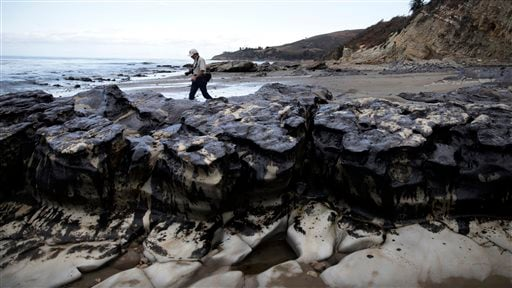 In this May 21, 2015 file photo, David Ledig, a national monument manager from the Bureau of Land Management, walks past rocks covered in oil at Refugio State Beach, north of Goleta, Calif.