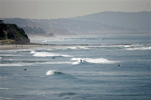 In this April, 2008, file photo, people swim and surf in the Pacific Ocean at Cardiff State Beach near Solana Beach, Calif., close to an area where a man was killed by a shark.