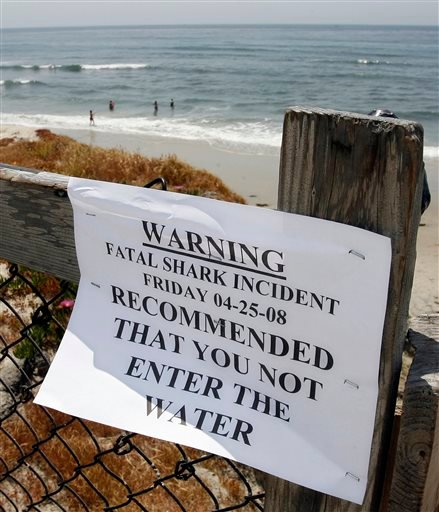 In this April 25, 2008, file photo, people enter the water near a shark warning sign at Cardiff State Beach in Encinitas, Calif.
