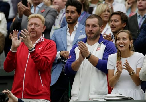 Jelena, wife of Novak Djokovic of Serbia, right and coach Boris Becker, celebrate after Djokovic won the men's singles final against Roger Federer of Switzerland at the All England Lawn Tennis Championships in Wimbledon, London, Sunday July 12, 2015. (AP