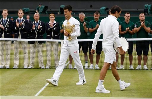 Novak Djokovic of Serbia, left, and Roger Federer of Switzerland hold their trophies after Djokovic won the men's singles final at the All England Lawn Tennis Championships in Wimbledon, London, Sunday July 12, 2015. Djokovic won the match 7-6, 6-7, 6-4,